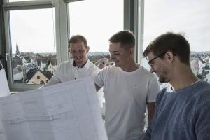 Drei Männer freuen sich beim Betrachten eines Architekturplans.